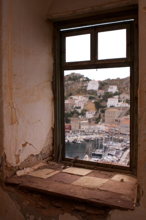 A window in an old building looking onto a town