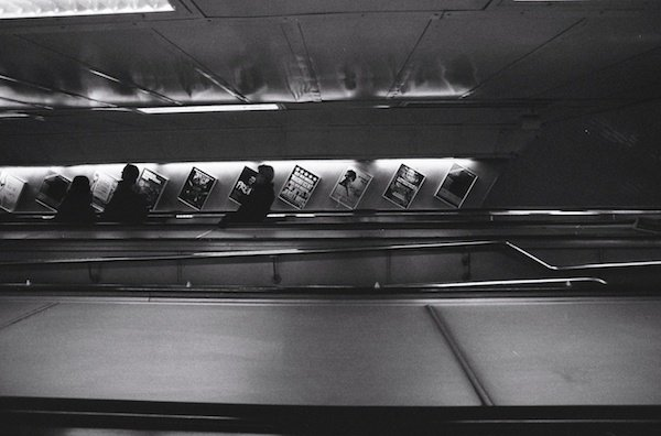 a dark image of people riding the underground escalators - black and white street photography