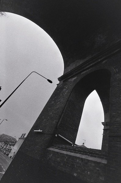 A slanted perspective of an arch and window - black and white street photography