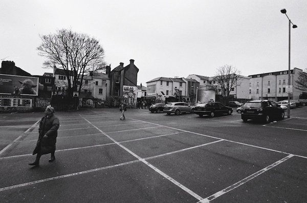 A woman walks in front of cars in a car park - black and white street photography
