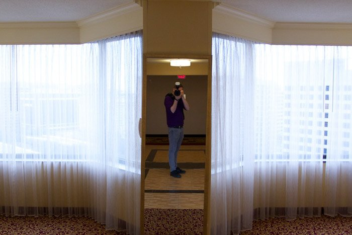 A portrait of the photography shooting a self portrait in the mirror - photography exposure tips