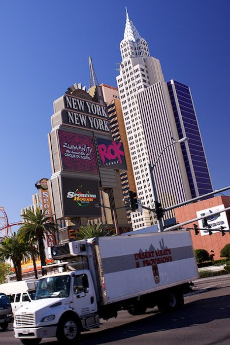 The facade of buildings in Las Vegas in the background of a busy street