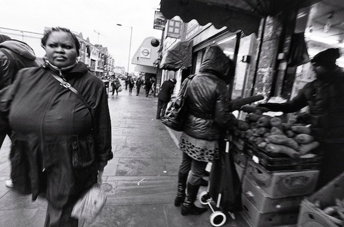 A black and white image of people walking through an outdoor market - shoot from the hip photography