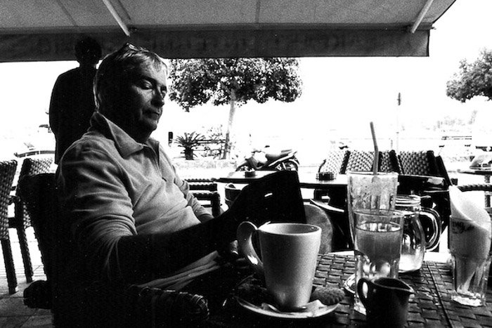 A monochrome portrait of a man in a cafe shot from the hip