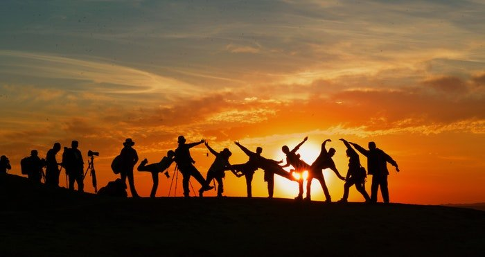 A group of photographers silhouetted against a sunset