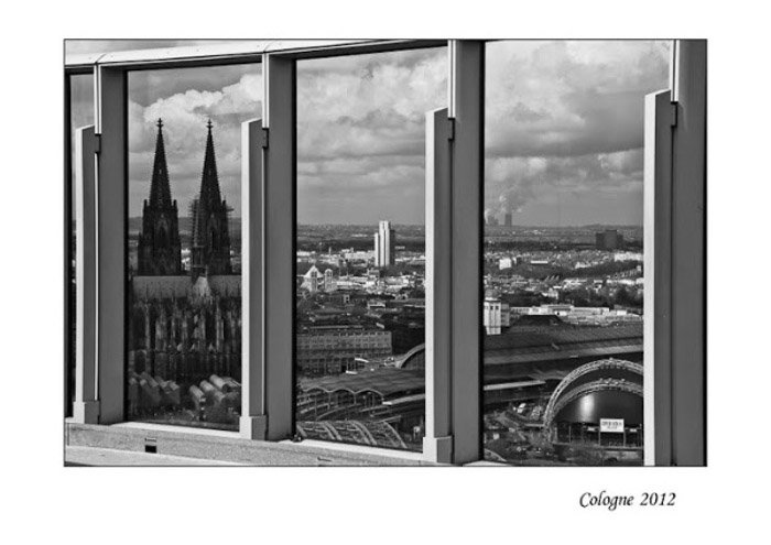 A black and white photo of a cityscape shot through a window