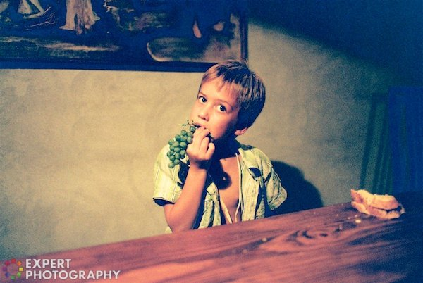 A little blond boy eating grapes in a dimly lit room behind a wooden desk