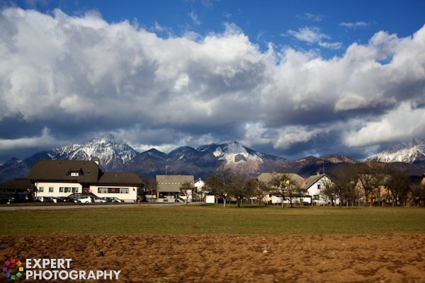 beautiful mountains with ordinary suburban houses, grass, clouds