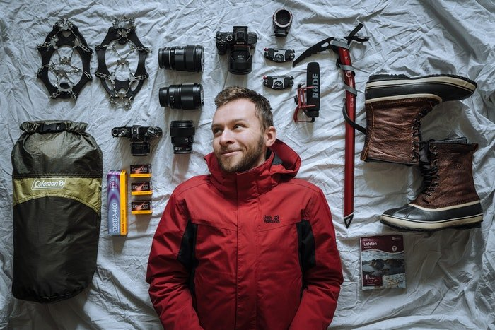 Man laying next to camera equipment laid out on a bed