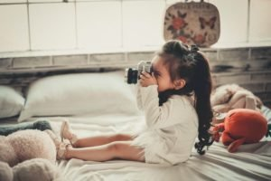 Cute little girl with a camera sitting on a bed