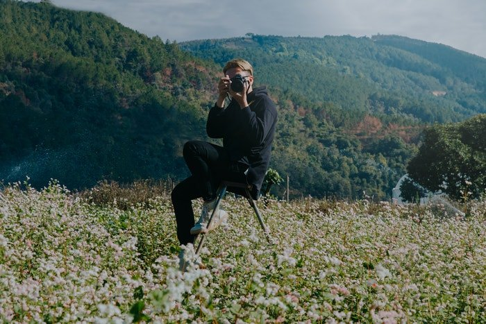 Amateur photographer in a field of flowers