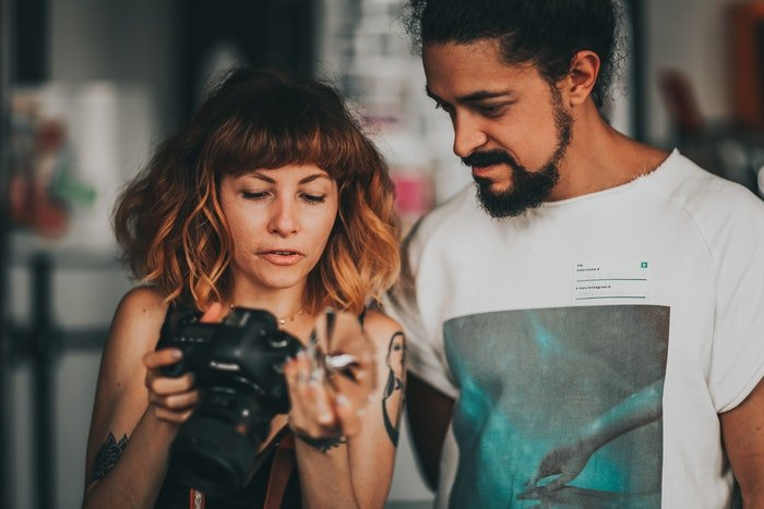 Woman holding a camera and showing the screen to the man next to her
