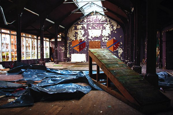 Hall of an abandoned boarding school with ruined walls and natural light coming in from the top