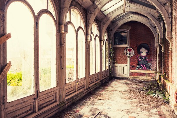 Dirty corridor of an old boarding school building with big windows and natural light and cute graffiti on the back wall