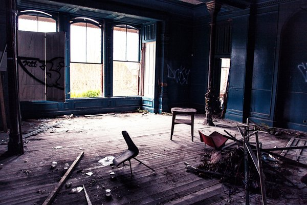 Room in an abandoned building with big windows, dark painted walls and broken wood and chairs
