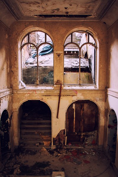 Abandoned building from the inside, two windows looking out to a ruined rooftop and a dark staircase leading up.