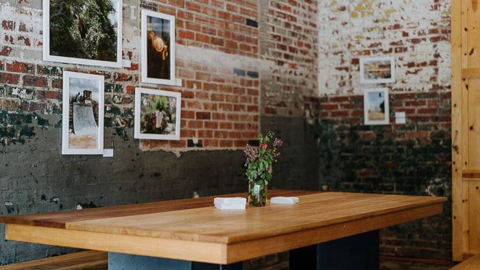 A wooden table in a rustically designed room with framed photography on the wall