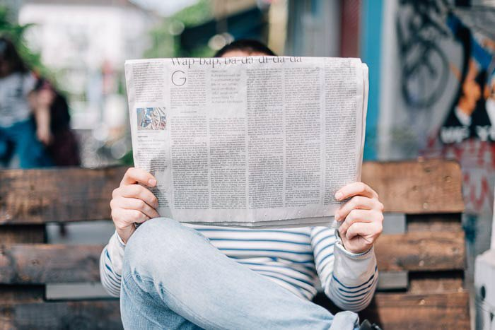 A straight on shot of a man sitting on a bench reading a newspaper