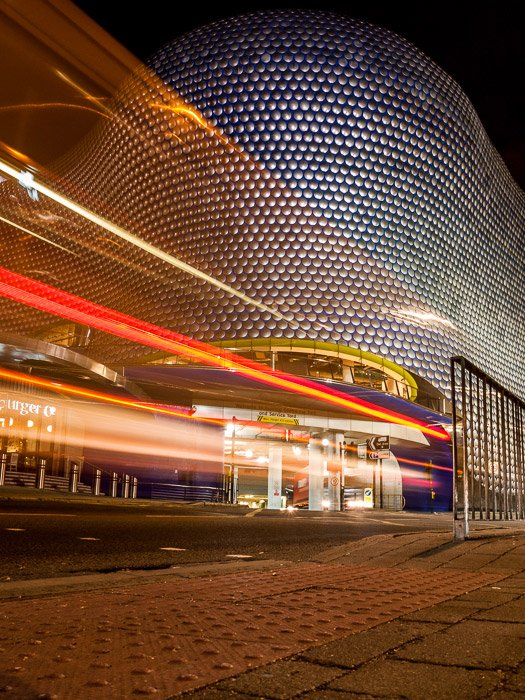 The coloured motion blur of light trails in front of the Bullring shopping center in Birmingham, UK.
