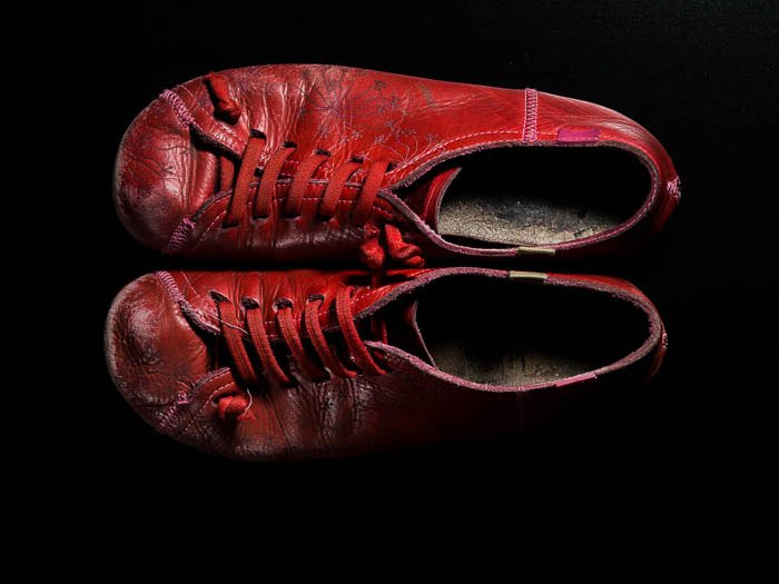 a pair of red camper shoes on black background
