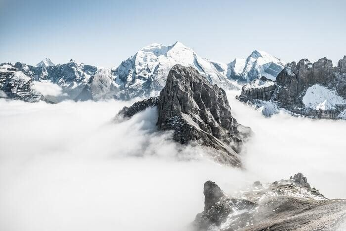 Photo of a high mountain peak with clouds around it