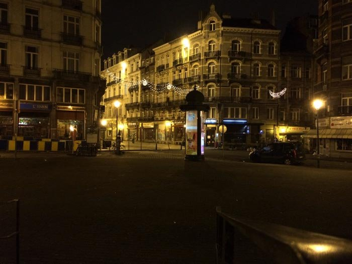 A picture of a street in Brussels at night