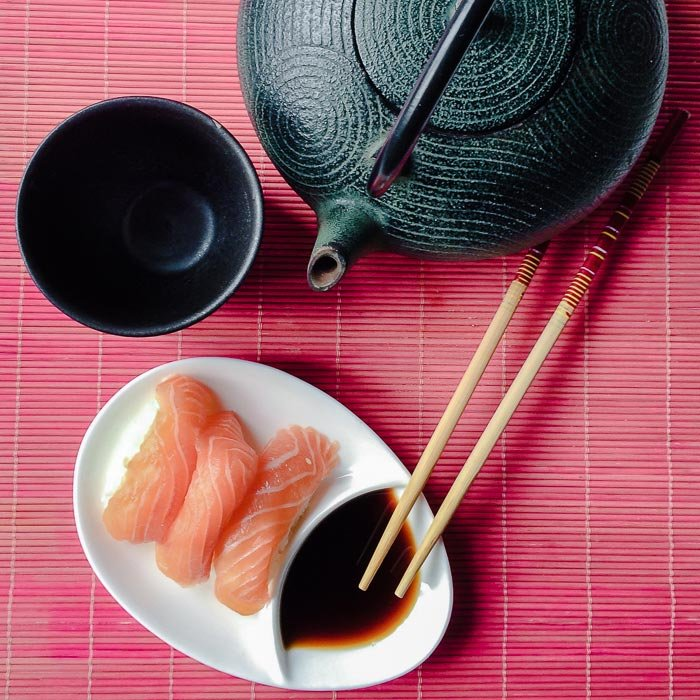 Three pieces of salmon nigiri on a plate with chopsticks and soy sauce and Japanese style teapot and cup next to it on a table
