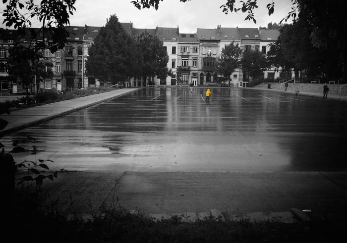 A black and white picture of a park in front of row houses with a child in the middle in a yellow coat