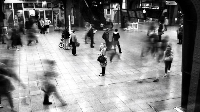 A black and white picture of people passing in the subway station