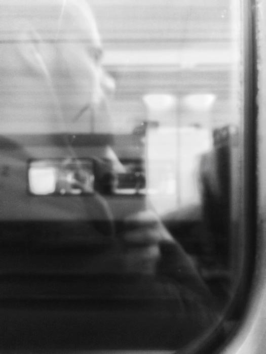A black and white picture of a man with headphones travelling by train with the other train reflection visible in the window