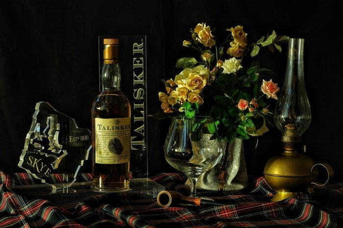 A still life shot of a bottle of whiskey arranged with rpops and flowers