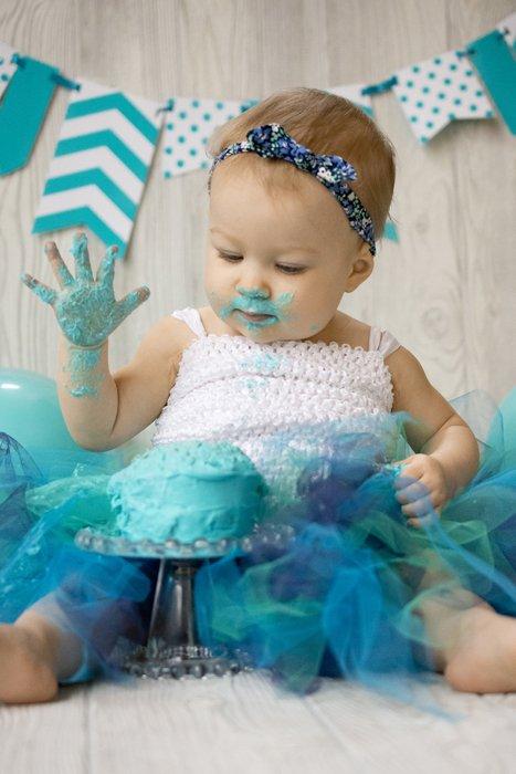 Cute diy cake smash photo shoot of a young baby smashing a green cake