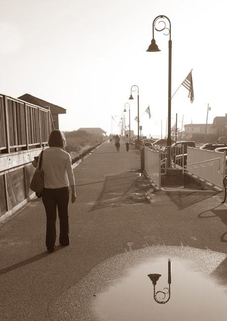 An image of a woman walking down a road where shadows are prevalent - Photography Projects to Do with Children