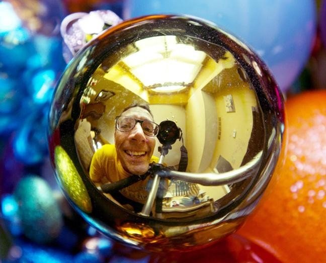 A photograph of a man seen in the reflection of a Christmas bauble - Photography Projects to Do with Children