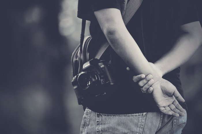 A black and white close up of a man with an inconspicuous camera with 50mm lens for taking candid street photos
