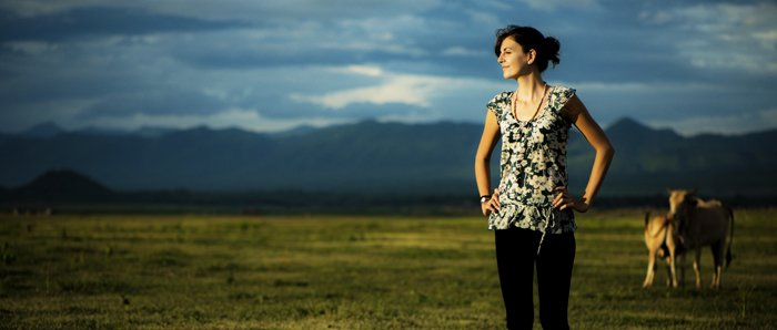 Photo of a woman outdoors with cows and mountains in the background