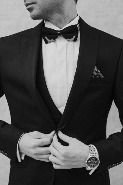 Black and white photo of a man in a black suit and bowtie