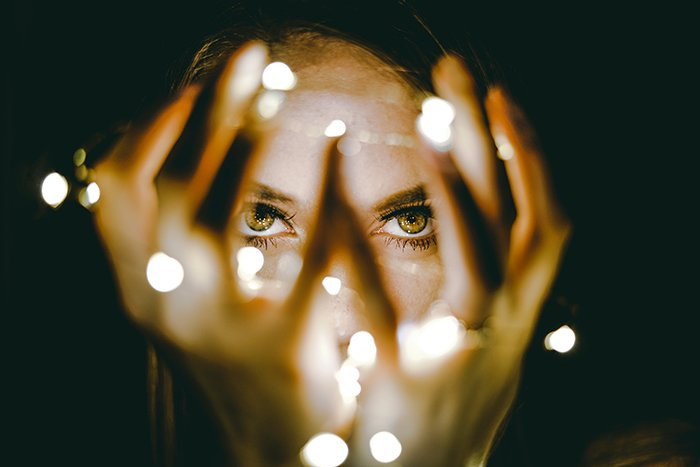 A girl poses for portrait photography with fairy lights out of focus