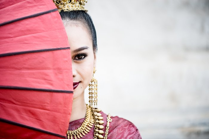 portrait photo of a girl with a red hand fan in front of her face