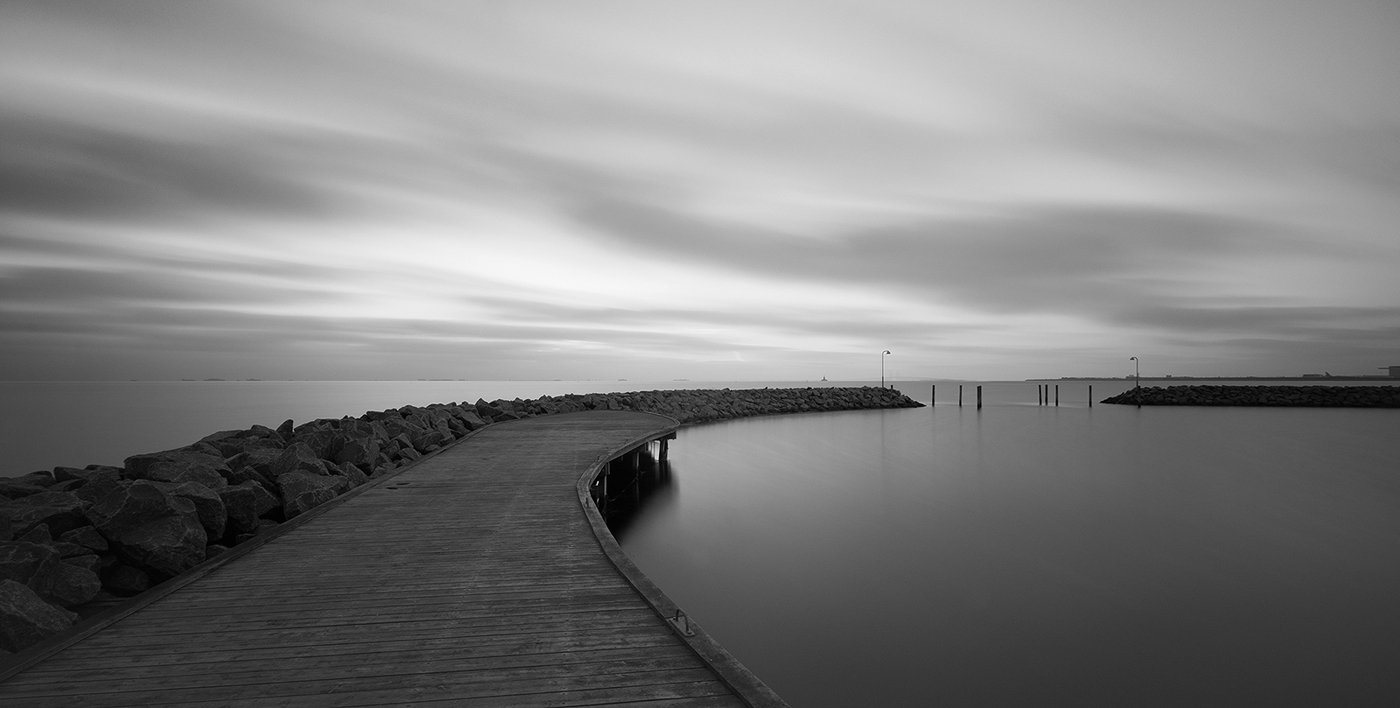 Monochrome image of water's edge with cloudy sky and still water