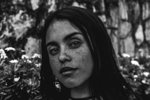 Black and white portrait of a woman with freckles