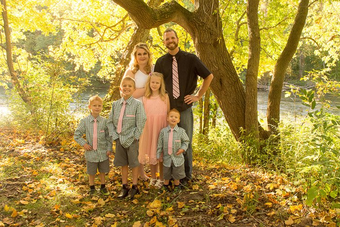 brighta nd airy porttrait of a family of 6 posed outdoors in golden hour