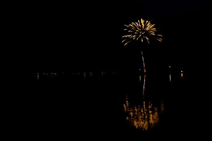 Amazing fireworks photography of yellow burst over water in the distance