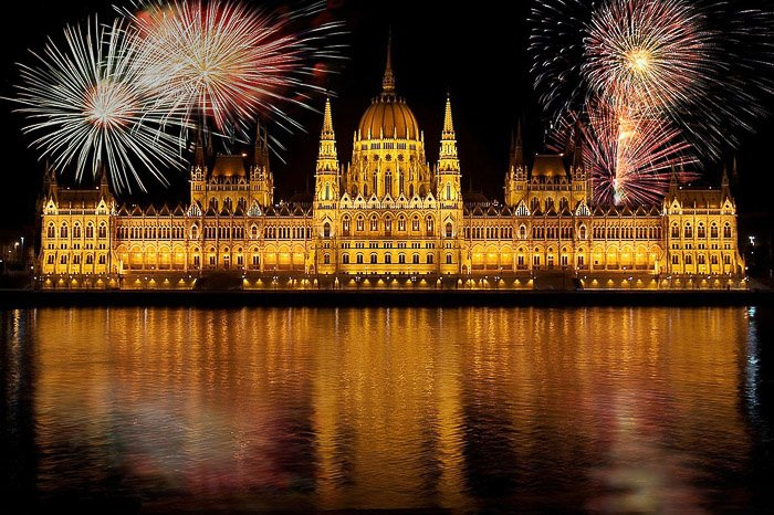 Stunning fireworks photograph of multiple large bursts over Budapest parliament building