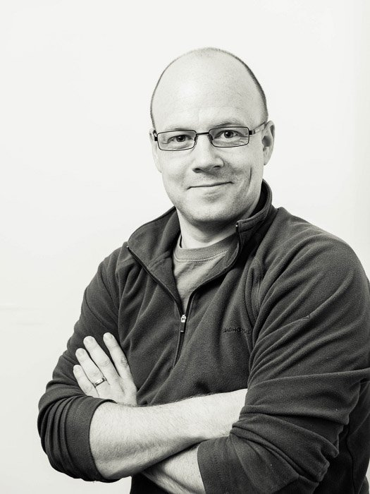 Black and white studio portrait of a man in glasses taken with loop lighting in studio
