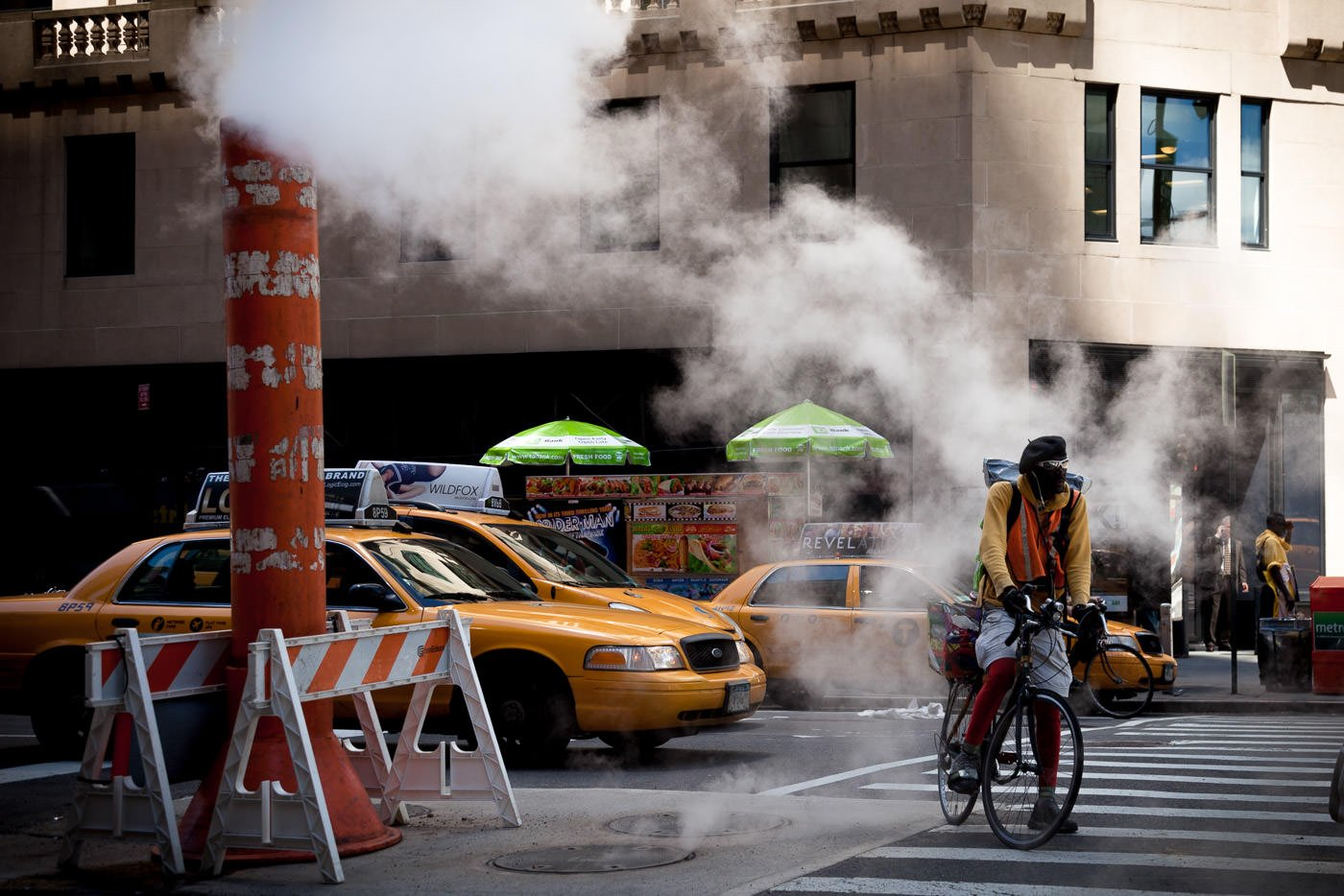 Street photography: NYC bike messenger in street with steampipe