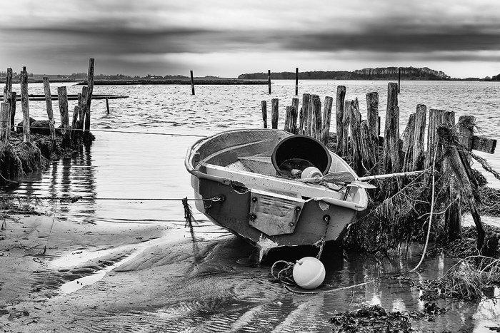 Black and white coastal photo showing small boat at low tide