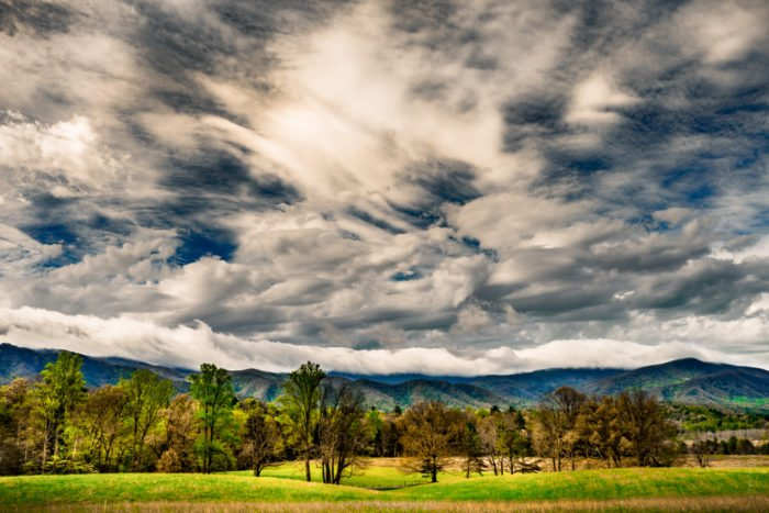 Dramatic Weather: Broad sky with multiple types of clouds over hills, fields, and forests