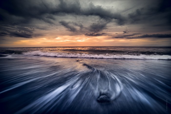 Dramatic Weather: Dark cloud cover at sunset on a beach