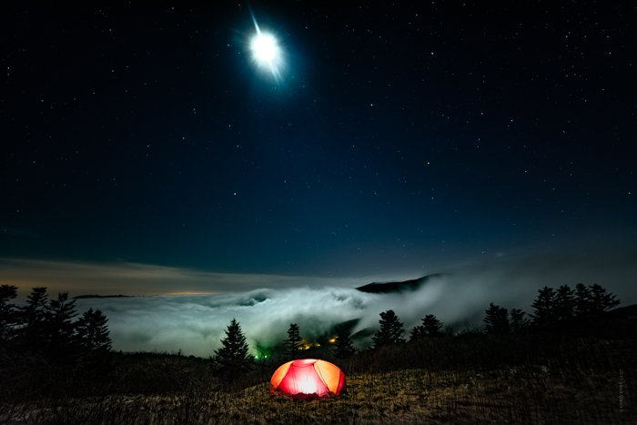 Dramatic Weather: Heavy fog rolling in on the horizon at night, with illuminated tent in foreground